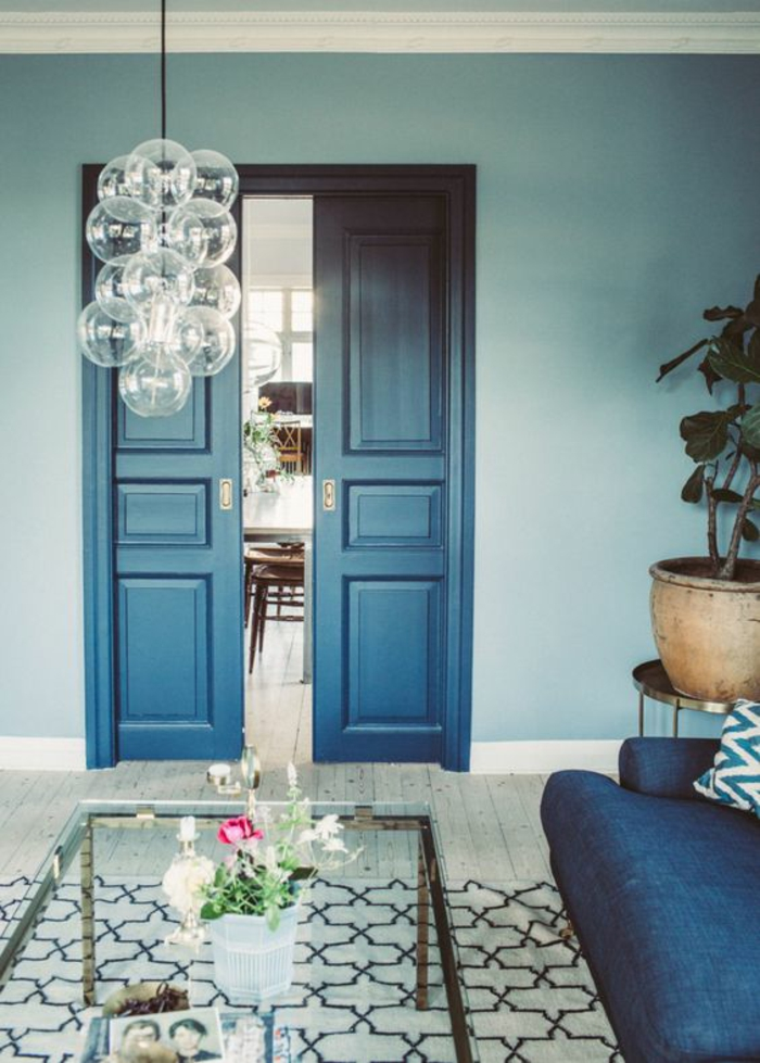 salon bleu petrole avec porte haute en couleur bleu gris azur couleur ambiance moderne avec luminaire avec des grandes boules en verre transparent