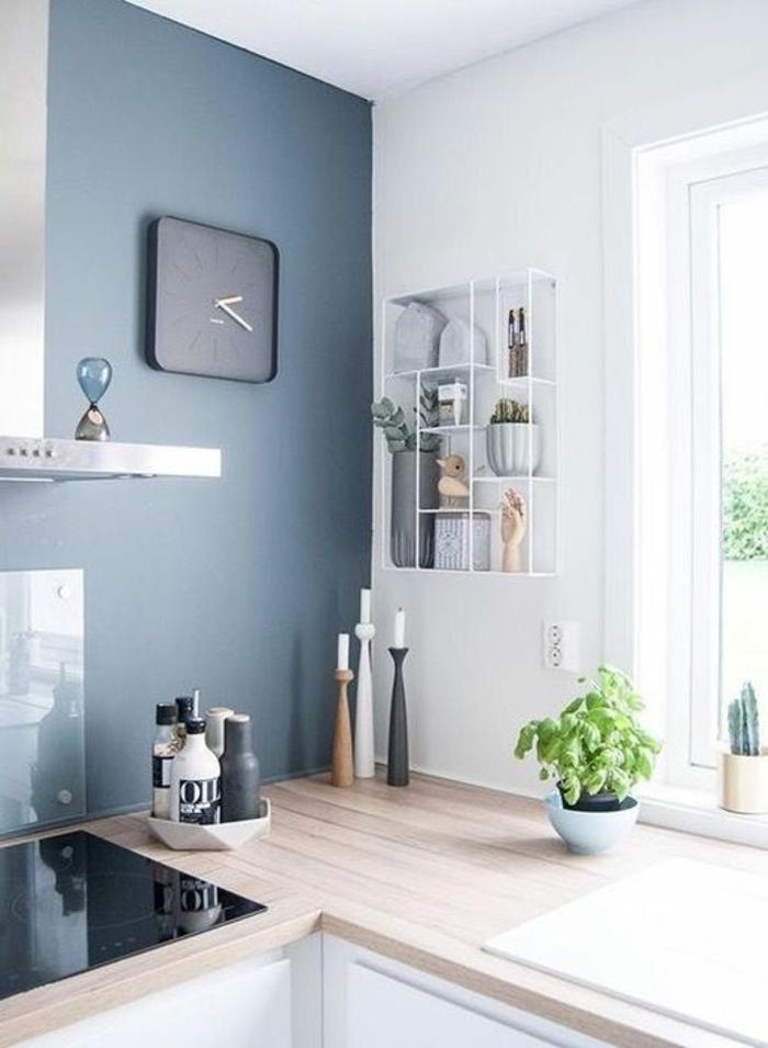 couleur bleu gris sur un mur d'une cuisine avec horloge électrique au cadran noir carré plan de travail en surface imitation bois clair PVC