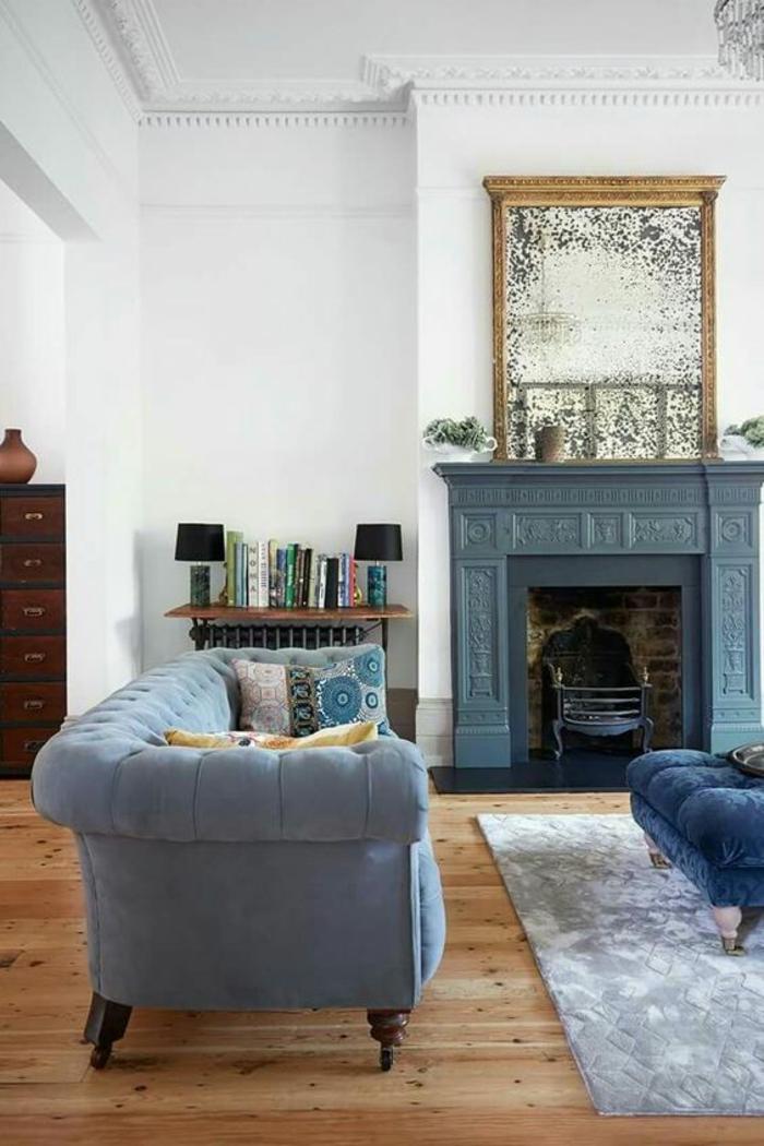 deco salon bleu canard avec grand canapé n velours gris clair et cheminée en bleu pétrole avec tapis en gris clair et blanc et meuble de rangement en marron foncé