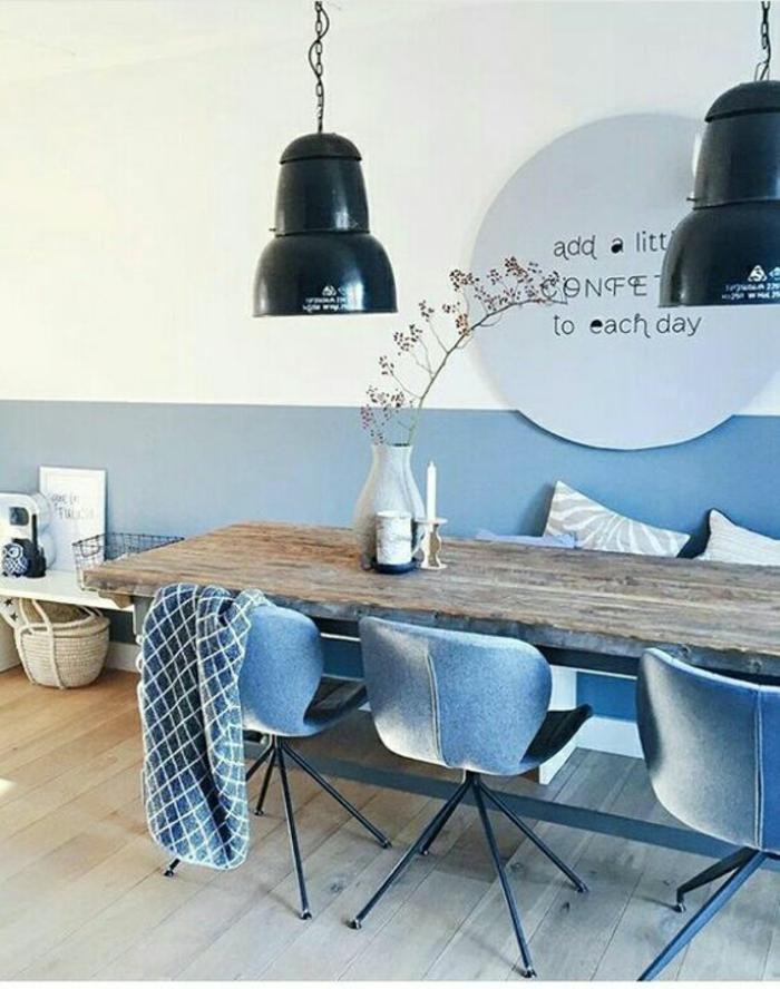 bleu cyan salle à manger en longueur meublée avec des fauteuils en couleur bleu gris en velours avec des grands luminaires noirs en style industriel