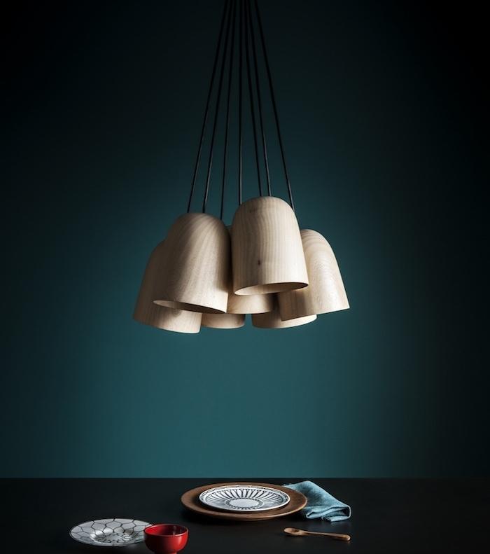 idée de peinture bleu pétrole sur un mur avec suspensions en bois, table noire et vaisselle blanc, noir et marron