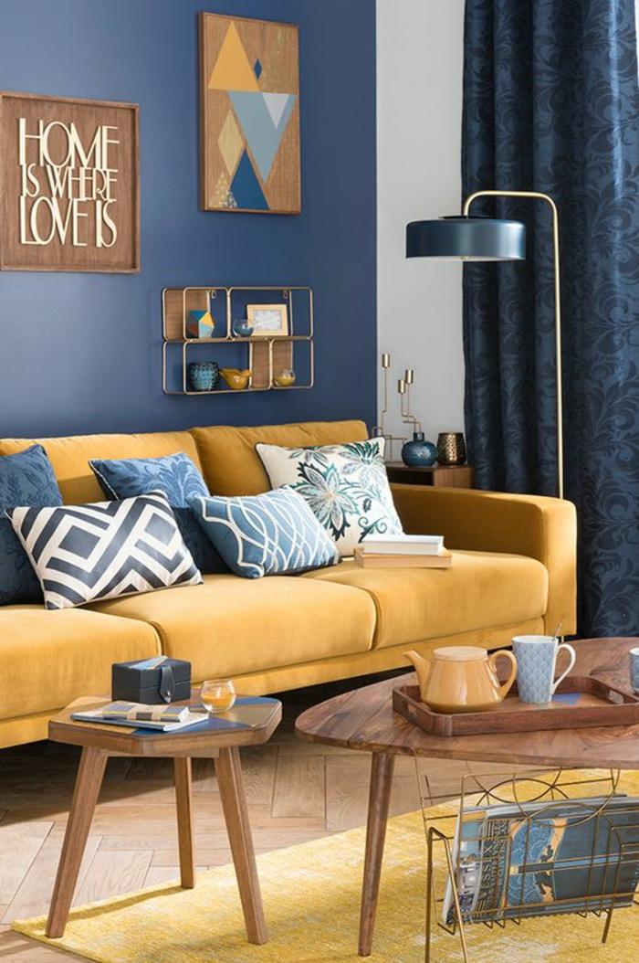 couleur bleu gris azur couleur dans le salon avec n canapé en couleur jaune moutarde avec des tableaux décoratifs aux murs et des rideaux en couleur bleu gris