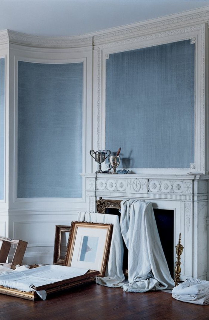 couleur bleu gris sur les murs d'une pièce en style classique en blanc et gris avec grande cheminée blanche et des grands tableax