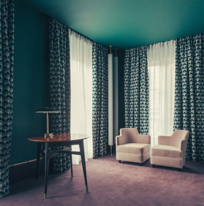 idee deco salon couleur bleu canard, nuance pétrole, fauteuils beiges, table en bois vintage, rideaux blanc, vert et bleu à motifs géométriques, tapis gris clair