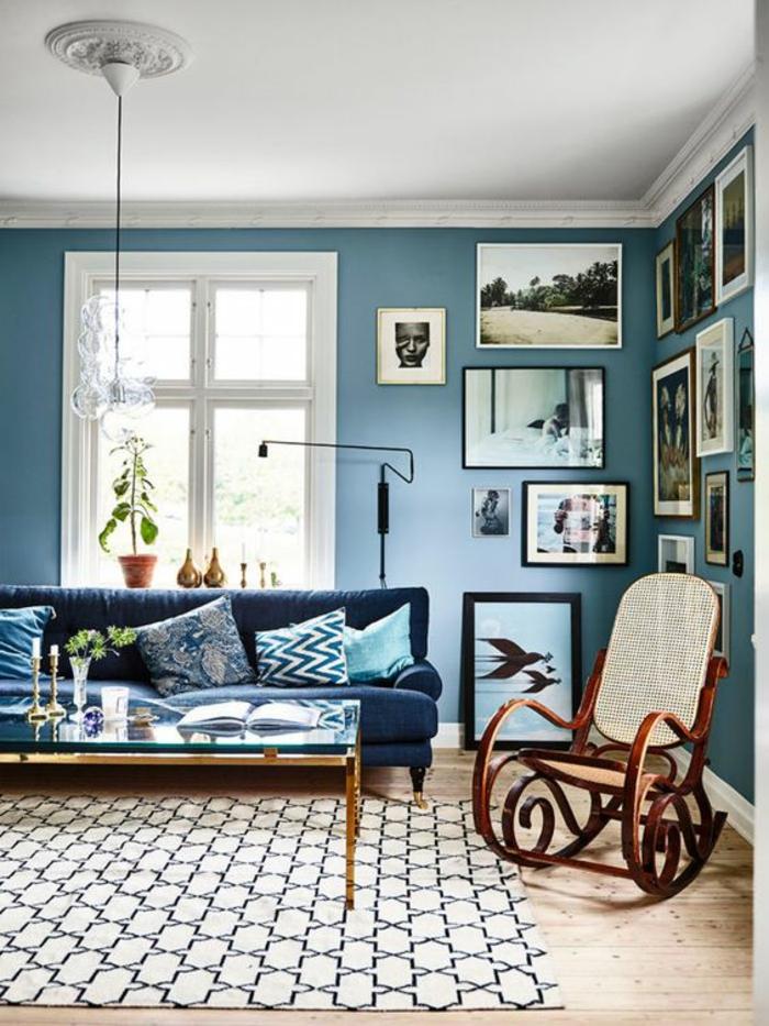 chambre adulte bleu avec chaise balançoire pièce en blanc et bleu avec canapé long en bleu canard et des murs très décorés avec des tableaux