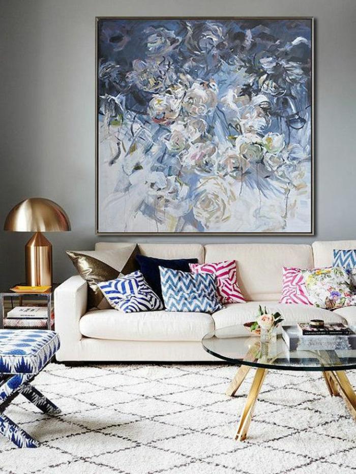 nuance de bleu sur un grand tableau avec des grandes fleurs dans des nuances différentes du bleu couleur reprise sur les meubles et sur les coussins