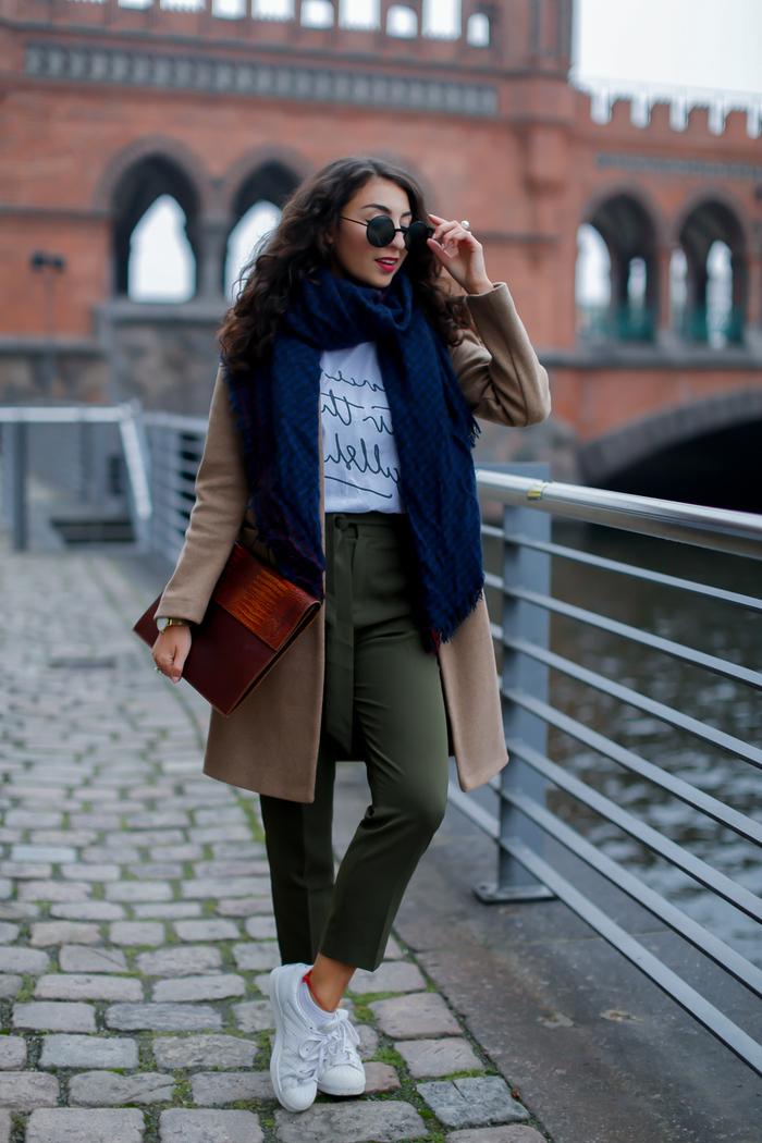 leçons de style pour la tenue pantalon kaki parfaite, un pantalon kaki à taille haute combiné avec un t-shirt à écriture manuscrite et un manteau long camel