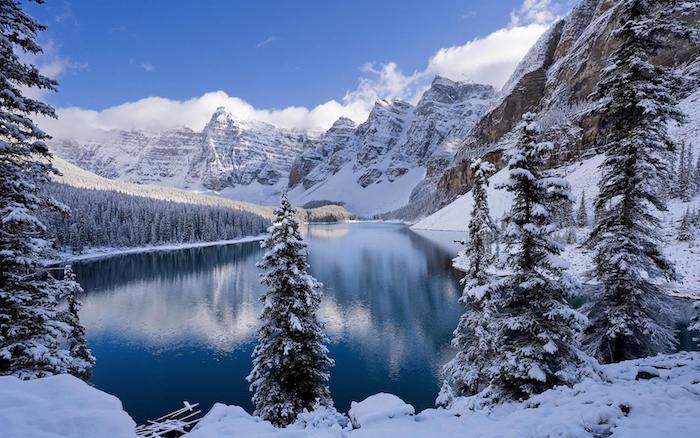 paysage hiver fond ecran, lac entouré de montagnes enneigées, arbres conifères et pins couverts de neige