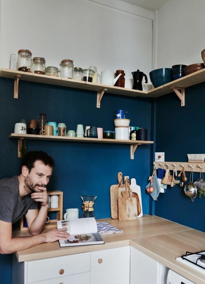 cuisine bleu canard, meuble blanc, avec surface en beige et marron, partie haute du mur en blanc, des accessoires en bois clair, coin bien optimisé