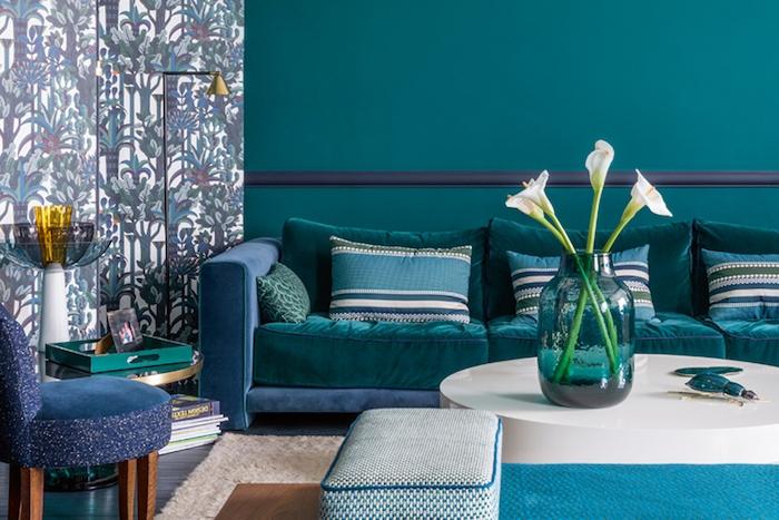 modele de salon bleu petrole, peinture murale couleur canard, coussins bleu, vert et blanc, canapé bleu marine et bleu paon, papier peint motif tropicaux, table basse blanche minimaliste
