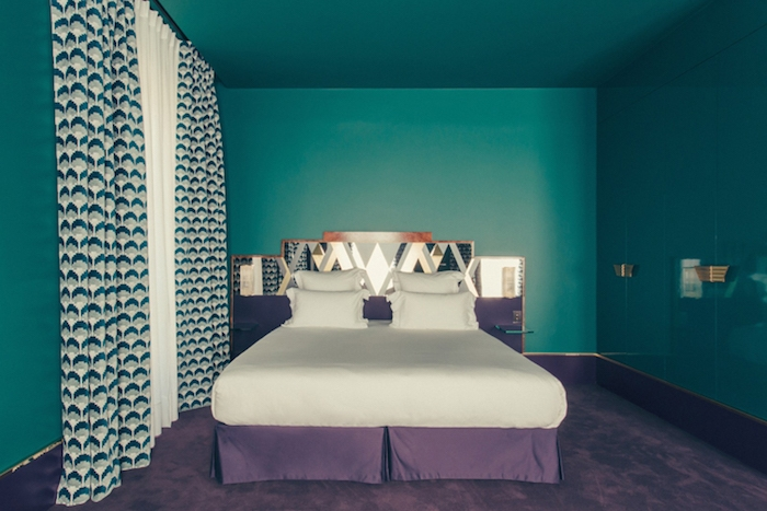 peinture bleu pétrole pour repeindre les murs d une chambre, linge de lit blanc et violet et tapis couleur violette, rideau blanc, gris et vert à motifs géométriques