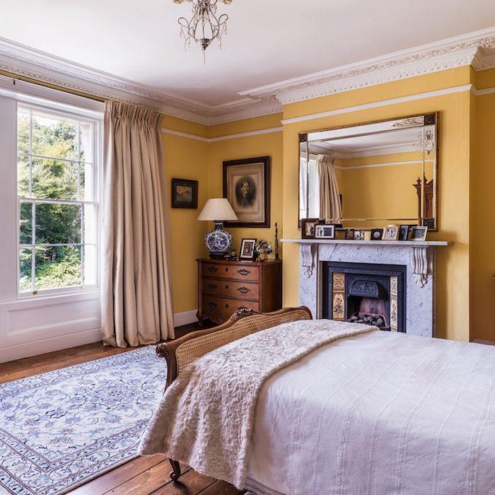 peinture chambre adulte jaune dans une pièce vintage, lit bois et commode vintage, linge de lit blanc, parquet marron, cheminée design