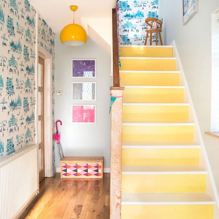 peinture escalier bois, effet ombré jaune sur les contremarches et marches blanches, rampe en bois et deco murale cage de papier peint blanc à motifs bleus, bord de mer, parquet en bois clair, deco murale de tableaux colorés, suspension jaune