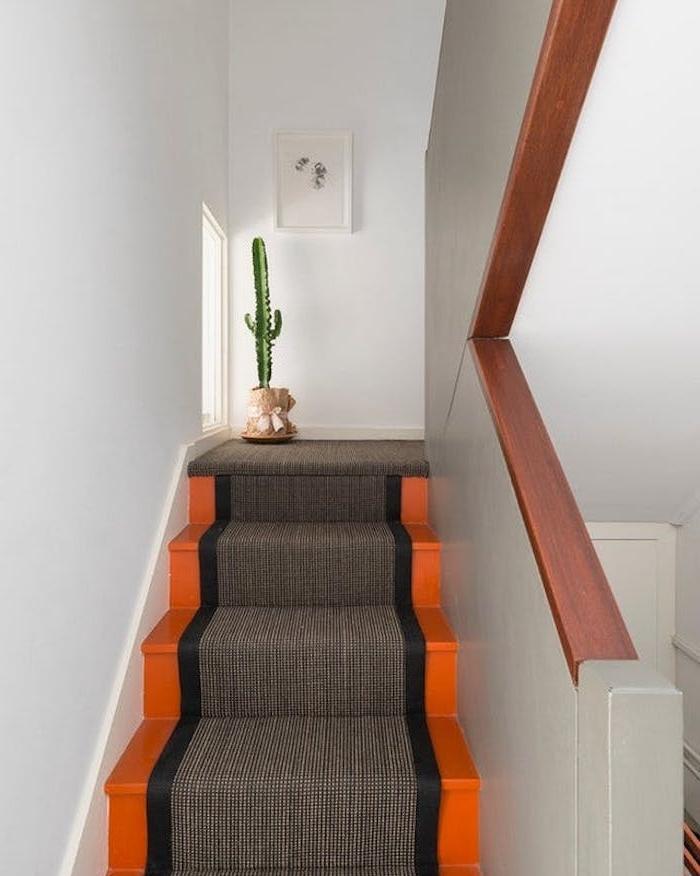 peinture escalier orange avec un tapis escalier gris et noir, une decoration verte de cactus dans un pot de fleur enveloppé de papier kraft