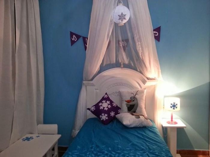 aménagement chambre enfant aux murs bleus, tête de lit en bois peint blanc, housse de coussins à design Olaf