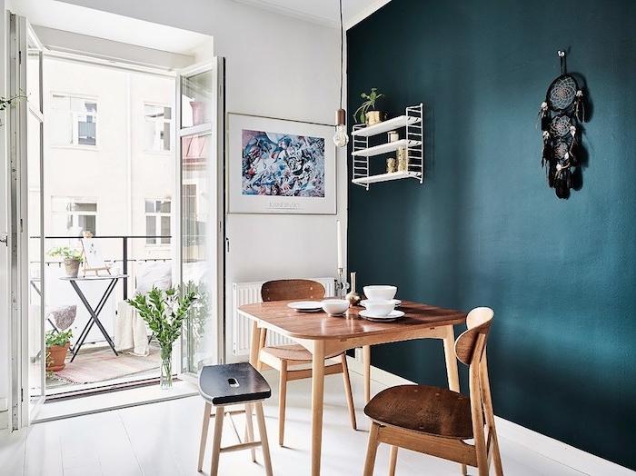 deco salle a manger avec un pan de mur pétrole, nuance de bleu foncée, table et chaises en bois, sol blanc, deco murale d attrape reve noir