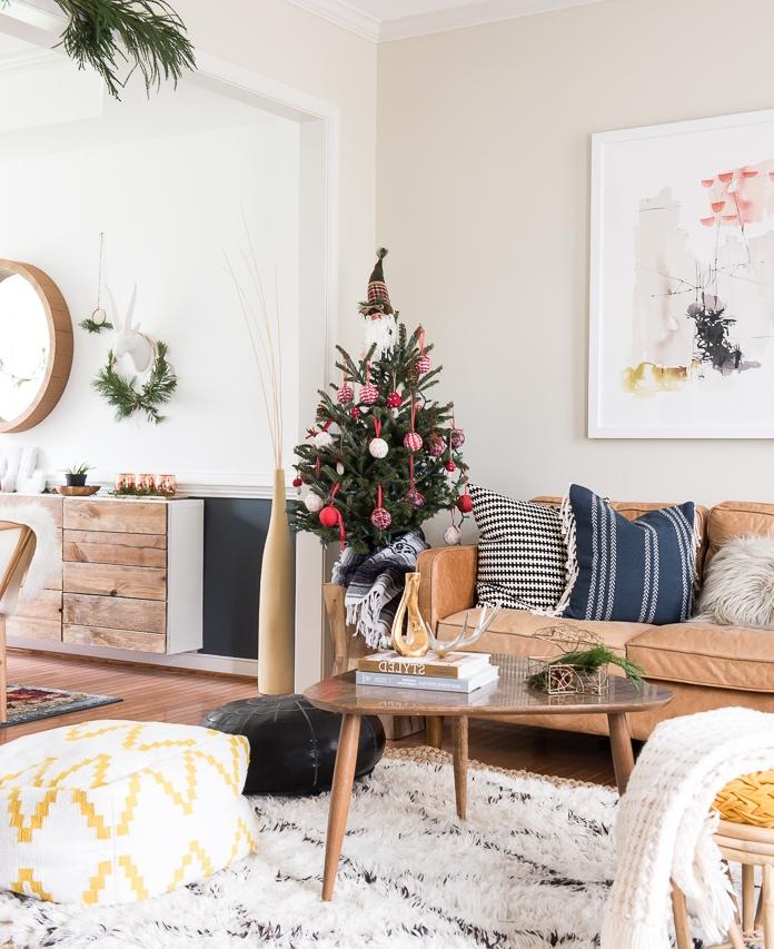 salon scandinave avec decoration sapin de noel en boules de noel rouges et blanches et poupée nain de père noel en tip, canapé marron, table basse en bois et tapis blanc moelleux