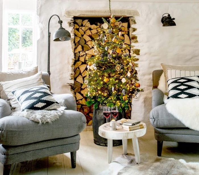 sapin de noel naturel en ornements et rondelles orange et guirlande lumineuse, canapé et fauteuil gris, tapis de fourrure animal, parquet clair