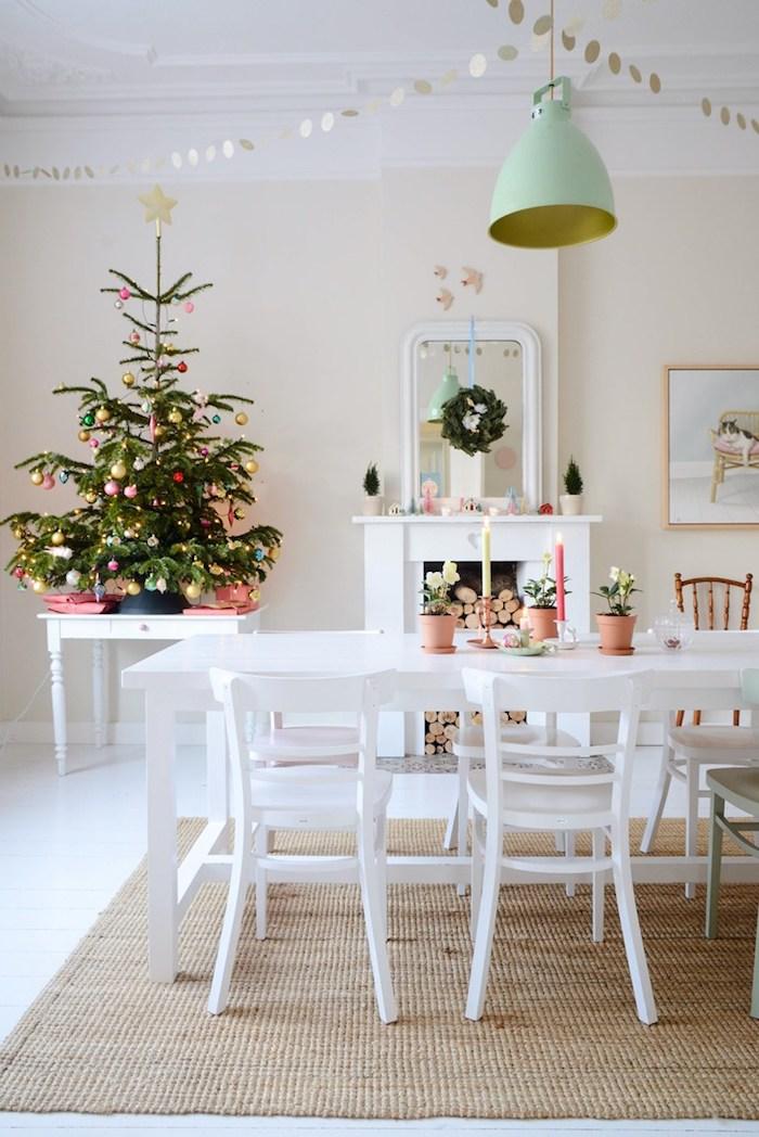 petit sapin de noel naturel décoré de boules de noel rouges, dorées, roses et blanches dans une salle à manger vintage scandinave, cheminée, chaises et table blanches