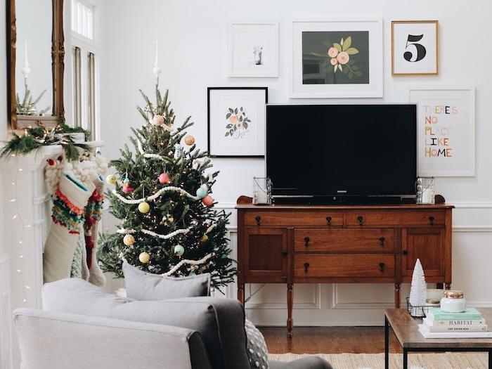 petit sapin de noel dans un angle de salon scandinave, boules de noel colorés en tons pastel, meuble tv vintage, fauteuil gris, chaussettes suspendues d une cheminée