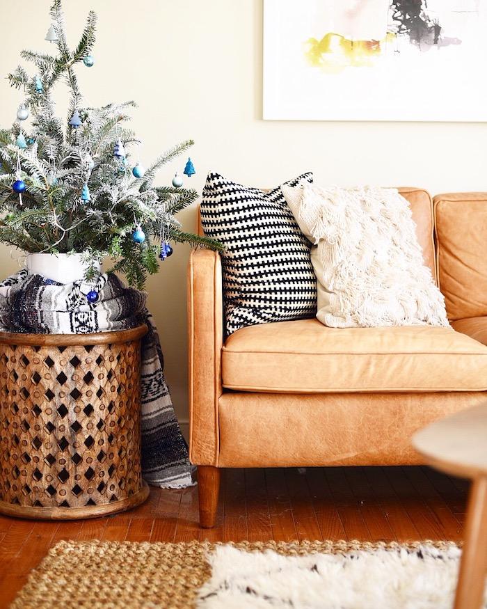 modele de petit sapin de noel aux branches blanchies avec decoration de boules de noel et figurines de sapin bleues, canapé marron avec coussins décoratifs