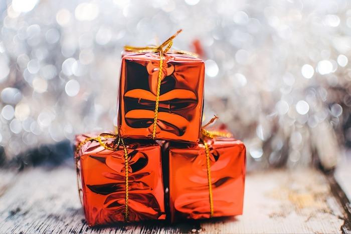 petits cadeaux emballage rouge avec ficelle dorée sur un fond blanc, guirlande argenté sur une table en bois, fond ecran noel simple