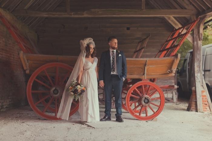 deoc champetre, une charette en bois comme fond pour une photo de couple mariés, femme en robe champetre blanche