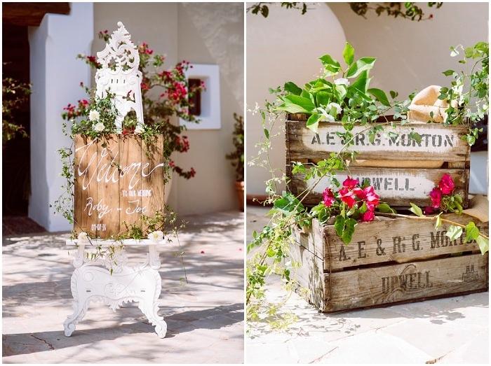 message bienvenue sur une planche en bois fleurie sur un chevalet vintage blanc, caisses de vin deco avec des fleurs et feuillages