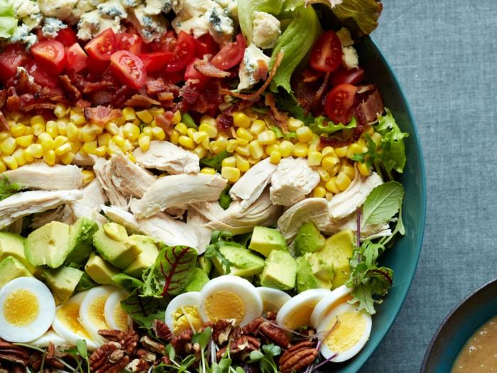 presentation salade composée, oeufs dûrs, avocats, viande, mais, tomates et fromage bleu