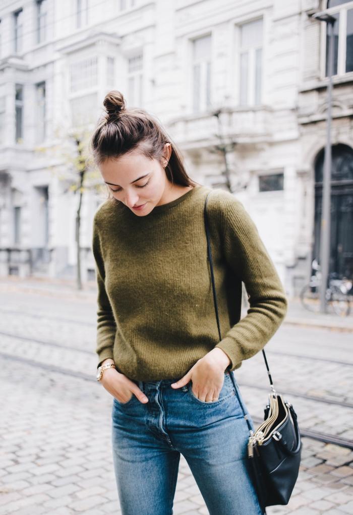look chaud et comfortable avec un pull douillet kaki vert glissé dans un jean