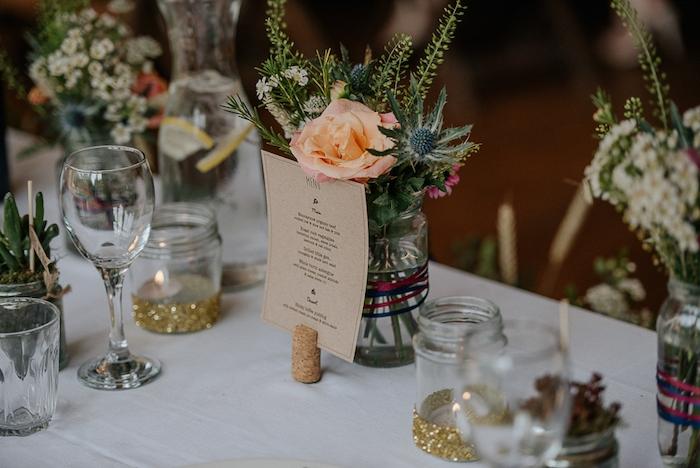 que faire avec des pots en verre, vases décorés de rubans, menu en papier kraft inséré dans un bouchon de liege, bougeoirs en paillettes, fleurs colorées, mariage chameptre