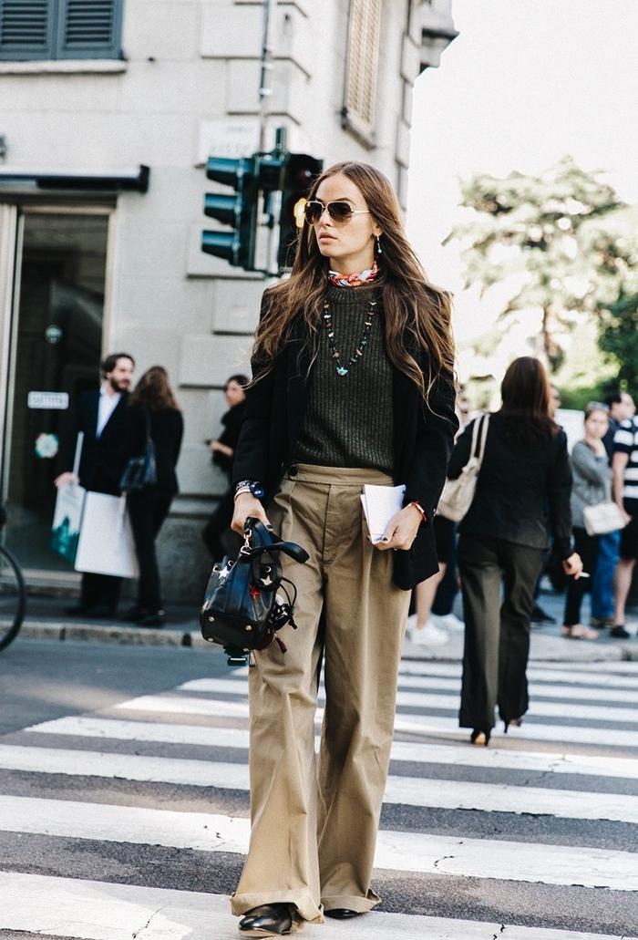 un souffle vintage avec une tenue pantalon kaki large et souple, un pull vert olive et un blazer noir cintré