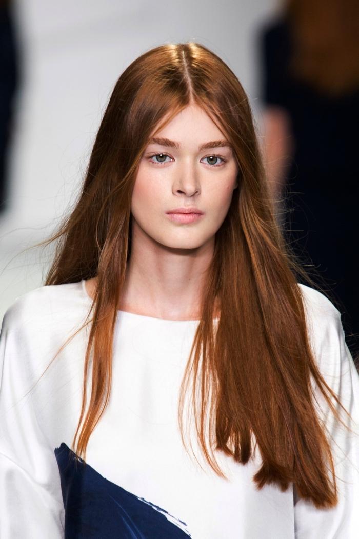 coloration cheveux longs de nuance cuivrés, coiffure femme aux cheveux raids, maquillage nude aux lèvres rose