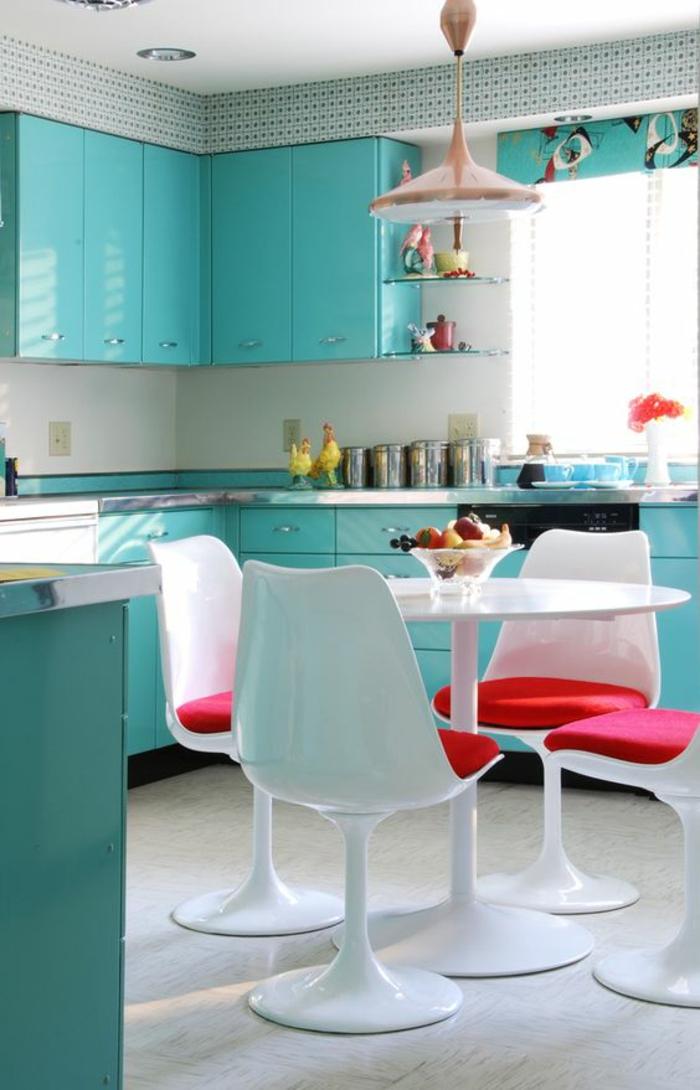 quelle couleur pour les murs d'une cuisine avec des meubles en bleu turquoise, luminaire rose, sol blanc, rideaux en bleu turquoise, rouge et marron, quatre chaises en plastique blanche, avec des coussins en fuchsia