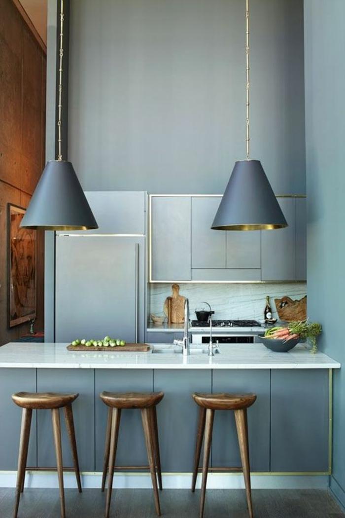 repeindre sa cuisine en bleu, quelle couleur pour les murs d'une cuisine, style industriel, murs et plafond hauts, luminaires avec des grands abat-jours suspendus longs gris fumée, sol en couleur marron, plan de travail en blanc lisse