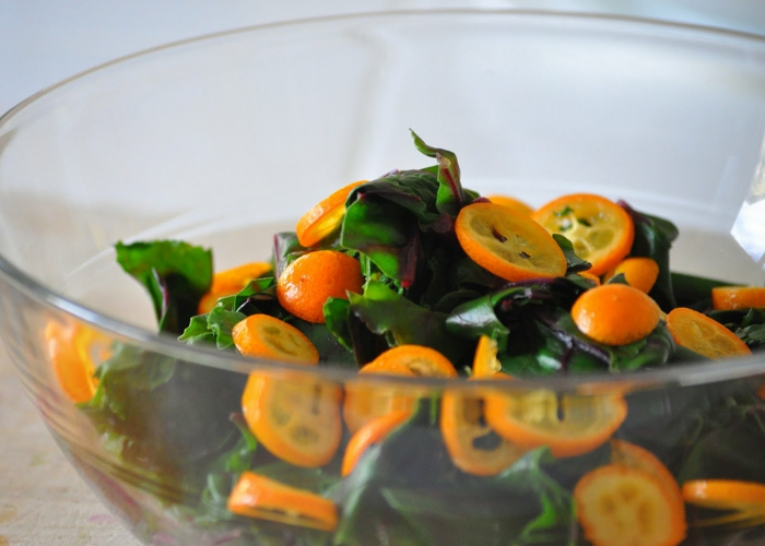 recette salade été, kumquats, feuilles de salade fraîche dans un bol en verre