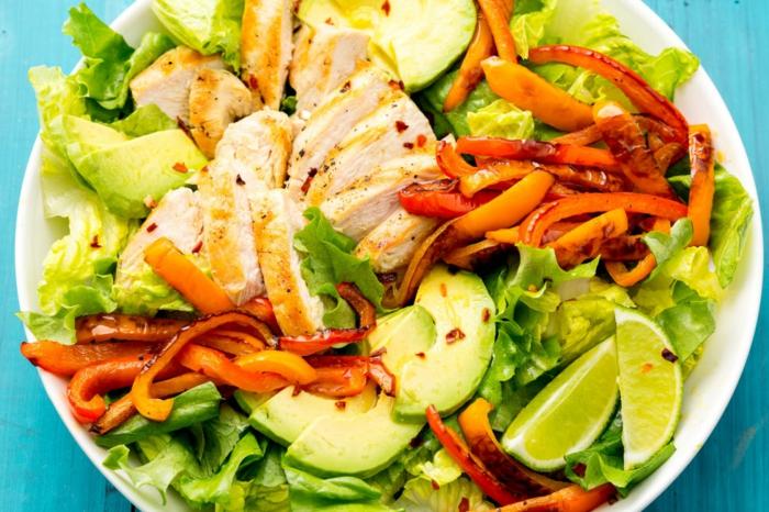 salade d'été pour barbecue, poulet rôti, avocat, carottes rôties, garnis de tranches de citron
