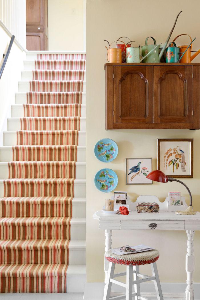 habillage escalier blanc en tapis à rayures marron, jaunes, et rouges, placard en bois avec des arrosoirs colorés, vureau vintage chic campagne, decoration à motifs floraux colorés