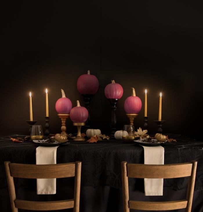 décoration de la table halloween avec nappe noire et bougeoirs en or, citrouilles peintes en rose sur table noir