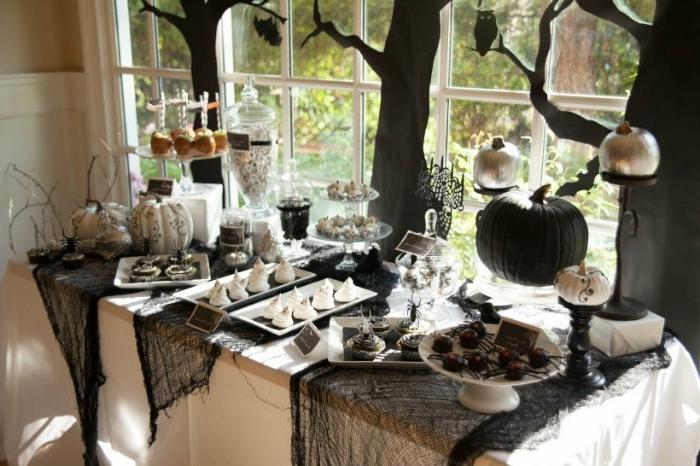 fête halloween avec table couverte de toile d'araignée noire, desserts et bonbons thématiques Halloween