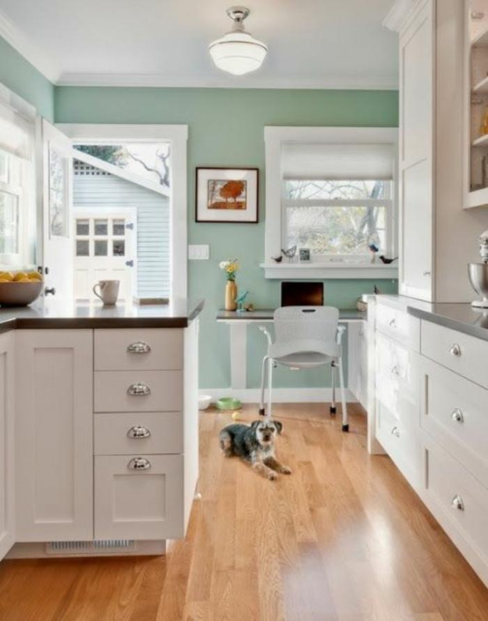 quelle couleur pour les murs d'une cuisine, murs en vert menthe, plafond en blanc, sol bois PVC en beige et marron, meubles blancs, avec des poignées en métal couleur argent, cadre blancs de porte et de fenêtres