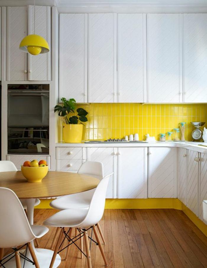 quelle couleur pour les murs d'une cuisine, briques jaunes et base jaune des meubles, luminaire en jaune en forme ronde avec une boule à l'intérieur, sol avec revêtement en parquet naturel, quatre chaises blanches en plastique, avec des pieds en bois clair, table ronde en bois PVC et plastique blanche
