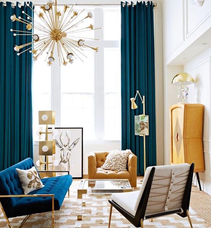 rideau bleu pétrole dans un salon spacieux, tapis blanc et jaune, canapé bleu marine, armoire et fauteuil jaune, décoration et suspension boule dorée