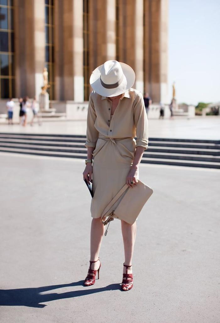look safari chic avec une robe kaki chemisier à manches retroussées et à la tailler serrée complétée par une pochette de la mêle couleur et un chapeau à large bord beige