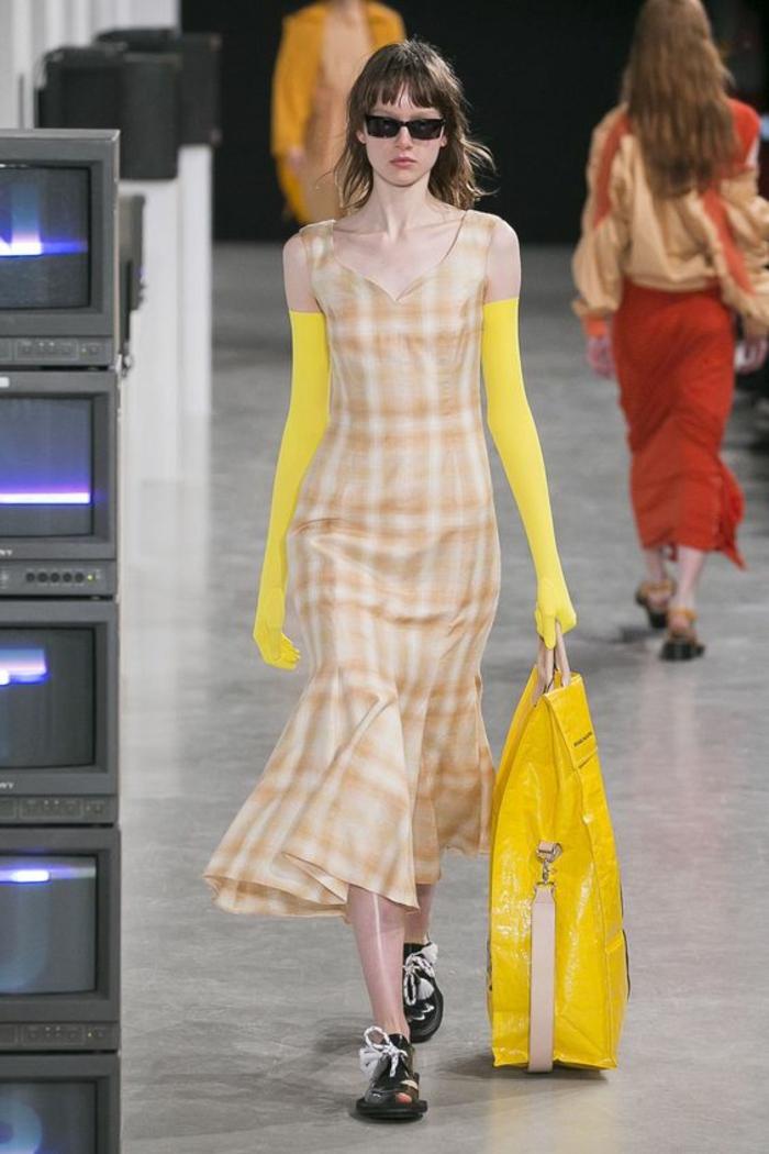 robe moulante longue aux motifs carreaux jaunes marrons t blancs portée avec des longues gants jaunes