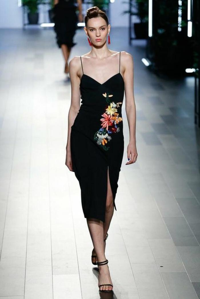 robe de soiree longue en noir avec fente profonde sur la jambe gauche et des bretelles ultra fines noires avec des broderies aux motifs floraux dans un style asiatique