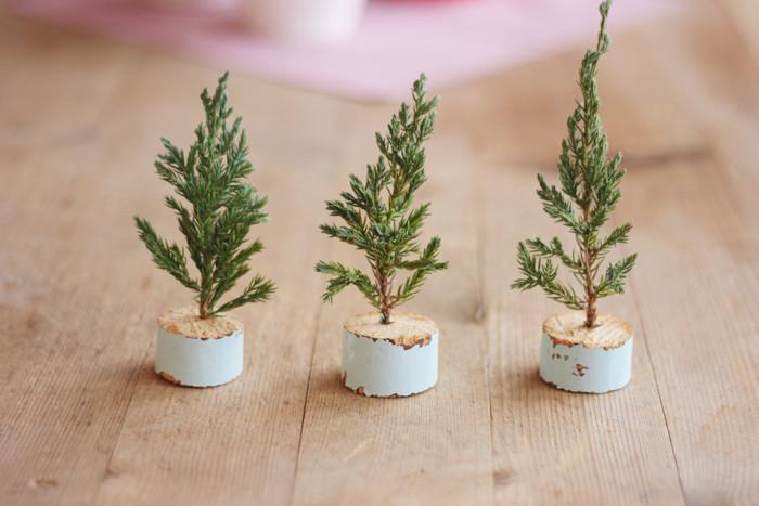 des brins de pin plantés dans des rondins en bois repeints de couleur bleu pastel, activité manuelle noel simple
