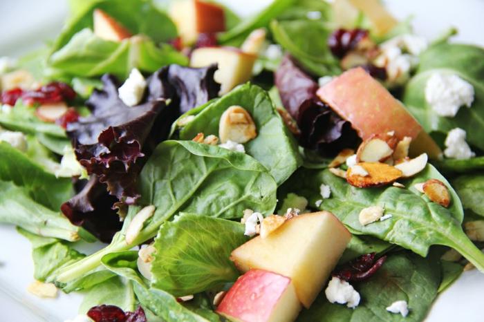 salade composé, pommes coupées en morceaux, noix et éînards au fromage jaune
