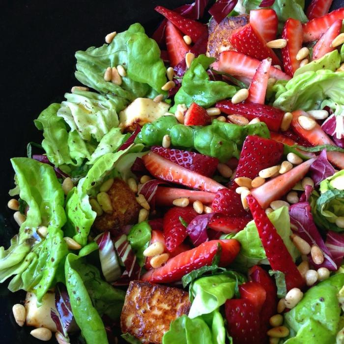 salade composée d'été, fraises découpées en morceaux fins, noix de pin, halloumi
