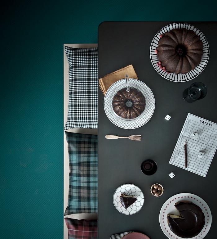 sol couleur pétrole, nuance de bleu, banc en bois avec des coussins rouge, gris, bleu et blanc, table grise avec des gâteaux